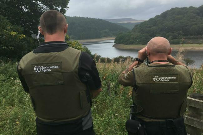 LOOKOUT: Environment Agency officers patrolling a river bank during the close season which forbids catching fish like barbel and chub