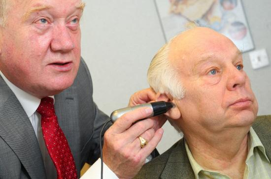 Chard & Ilminster News: £5 FOR LEGION: Ted Garrett, hearing aid audiologist, gives Bill Bestford a hearing test