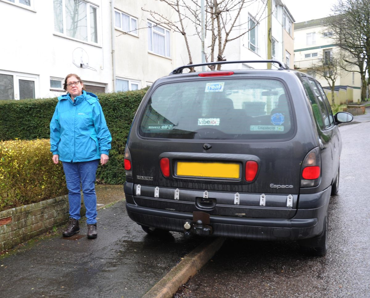 CLLR Jill Shortland next to a vehicle part-parked on the pavement.