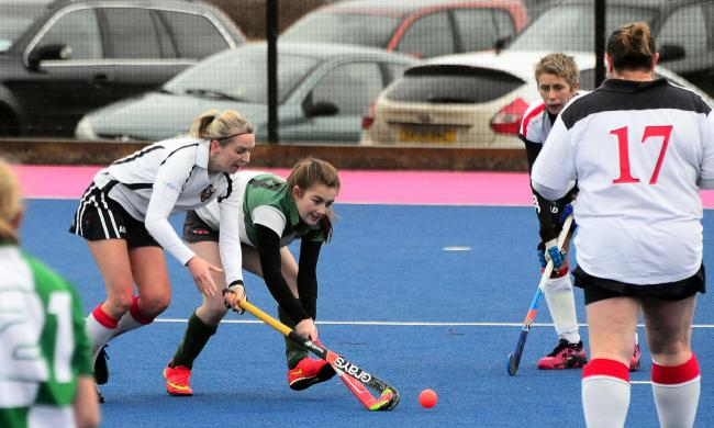 CONTEST: Chard ladies' Sasha Taylor (in green) in action against Taunton Vale 4ths. Pic: Ash Magill
