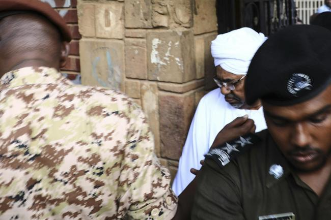 Sudan's deposed president Omar al-Bashir is escorted to a vehicle as he returns to prison